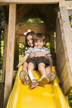 Hispanic girl hugging boy on top of slide smiling at viewer. photo