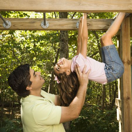 Hispanic girl hanging by arms and legs from monkey bars smiling at father helping her. photo