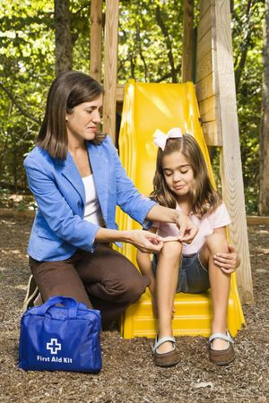 applies: Hispanic girl sitting on playground slide while woman applies first aid bandage to knee.