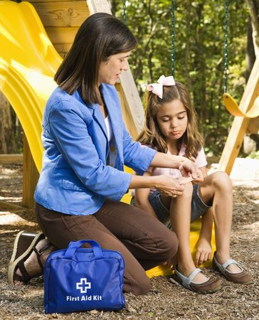 Hispanic girl sitting on playground slide while woman applies first aid bandage to knee. photo
