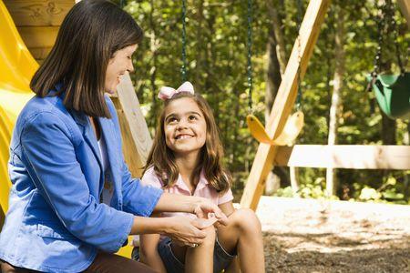 Hispanic girl sitting on playground slide smiling at woman applying first aid bandage to knee. Stock Photo
