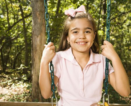 Hispanic girl sitting on playground swing smiling at viewer. photo