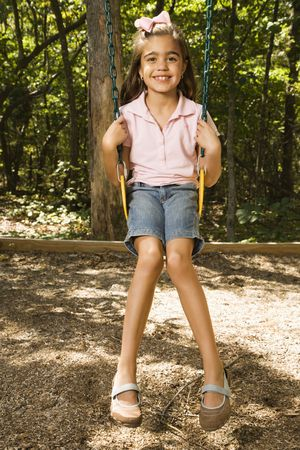 Hispanic girl sitting on playground swing smiling at viewer. photo