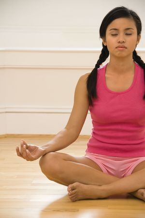 Young woman sitting on floor meditating in yoga lotus pose with legs crossed and eyes closed. photo
