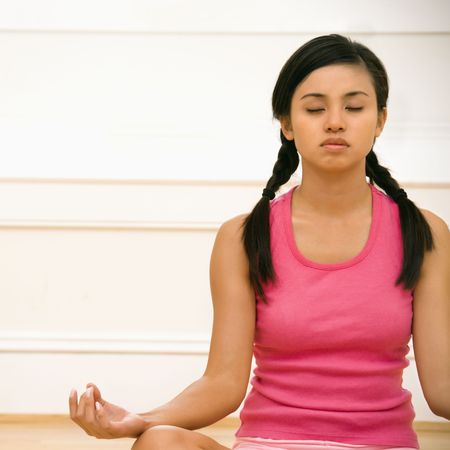 Young woman sitting on floor meditating in yoga lotus pose with legs crossed and eyes closed. Stock Photo - 2555605