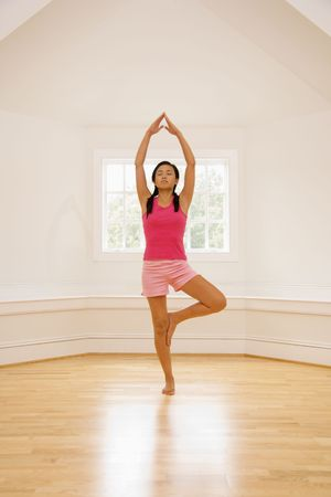 Young woman balancing in yoga tree pose. Stock Photo - 2555281