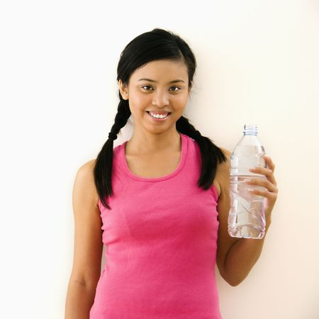Young woman in fitness outfit holding bottled water and smiling. Stock Photo - 2555647