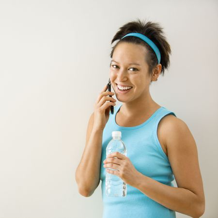 Young woman in fitness wear holding bottled water on cellphone smiling. photo