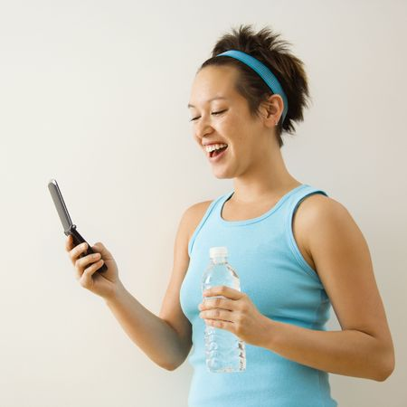 Young woman in fitness clothing holding bottled water and smiling at cellphone. photo
