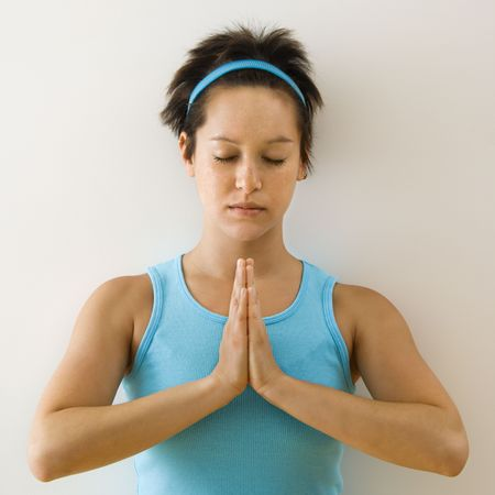 Young woman holding hands in prayer position with eyes closed meditating. Stock Photo - 2555699