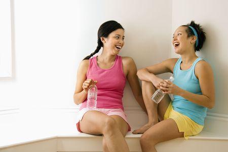 socializando: Dos mujeres j�venes en ropa de fitness celebraci�n botellas de agua sesi�n sonriente y ri�ndose y hablando.  Foto de archivo