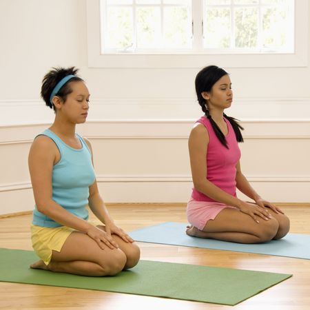 Two young women sitting on yoga mats with eyes closed. photo