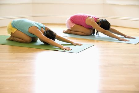 yoga class: Two young women on yoga mats doing childs pose.