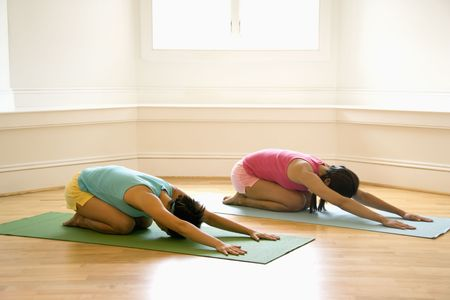female pose: Two young women on yoga mats doing childs pose.