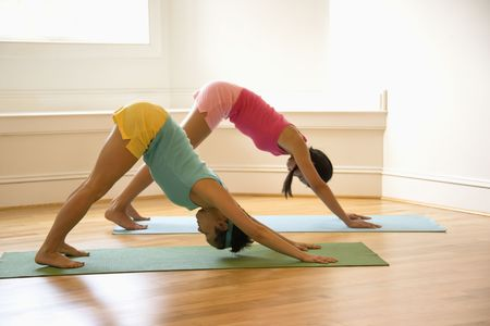 horizontal position: Two young women on yoga mats doing downward facing dog pose.