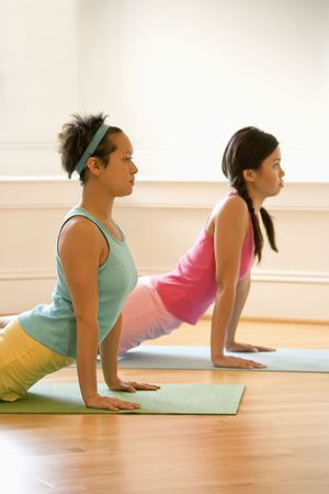 Two young women on yoga mats doing upward cobra pose. photo