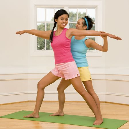 beginner: Young woman helping another young woman with positioning on her yoga pose.