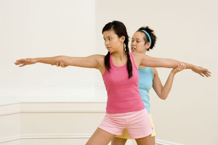 Junge Frau bei einer anderen jungen Frau, die Positionierung auf dem Yoga-Pose.