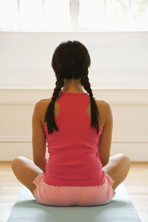holistic view: Rear view of young woman sitting on mat with legs crossed in yoga pose. Stock Photo