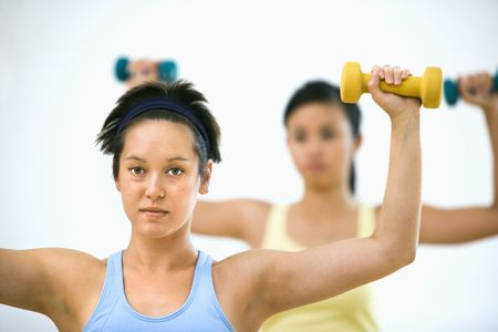 two tone: Young women at gym lifting hand weights. Stock Photo