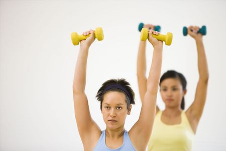 Young women at gym lifting hand weights. photo