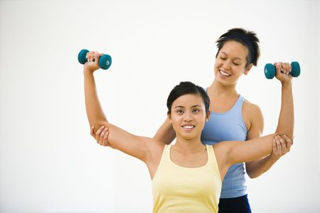 helps: Young woman lifting hand weights while another woman helps position her arms.