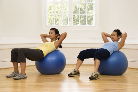 Two young women doing ab workout on balance balls. photo