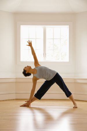 Young woman doing yoga triangle pose indoors by sunlit\ window.