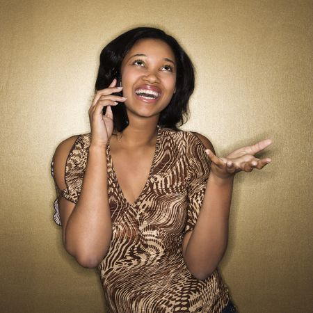 Young African-American young woman talking on cellphone smiling. photo