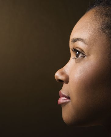 thinking woman: Close-up profile portrait of serious African-American young adult female.