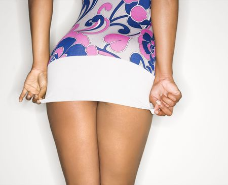 Young African-American female pulling down short dress over derriere. Stock Photo