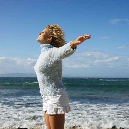 viento soplando: Muy joven rubia mujer de pie en Maui, Hawaii playa con los brazos a lado y el viento que sopla sonriente de pelo.