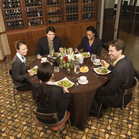 lunch meeting: High angle of group of businesspeople in restaurant dining.