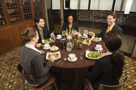 lunch meeting: High angle of diverse group of businesspeople in restaurant eating.