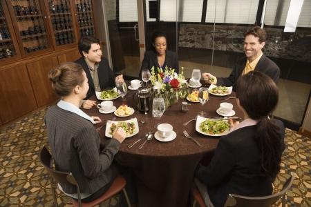 lunchen: Hoge hoek van diverse groep ondernemers in een restaurant eten.