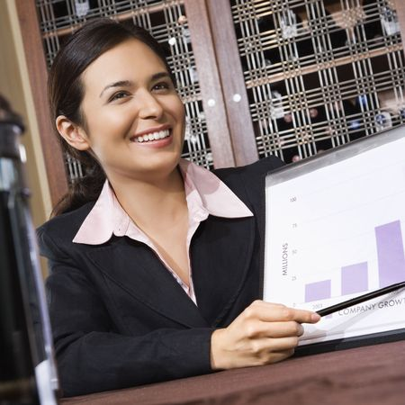 one to one meeting: Businesswoman smiling and pointing to bar graph. Stock Photo
