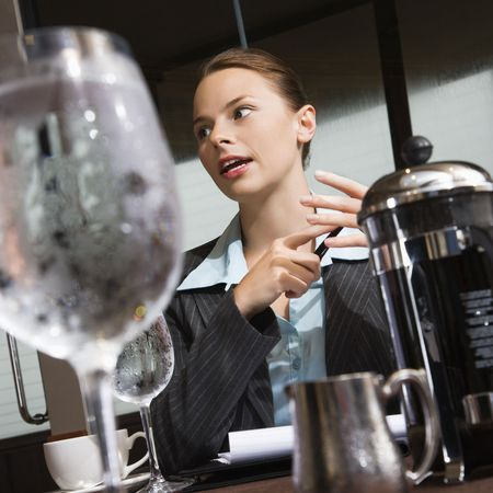 Caucasian businesswoman sitting at table with coffee and beverages. photo