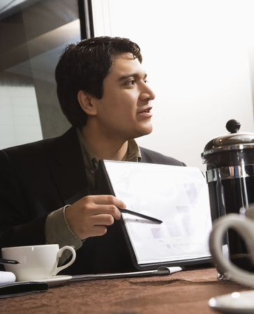 Businessman sitting at table pointing to bar graph. Stock Photo - 2615687