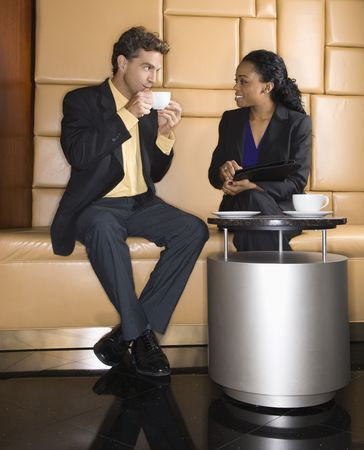 Caucasian businessman and African Amerian woman drinking coffee. Stock Photo - 2615846