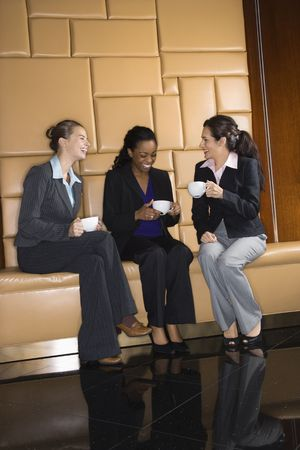 socializing: Businesswomen drinking coffee and conversing.