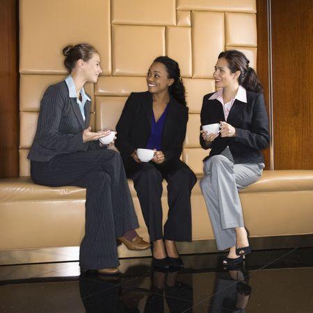 Businesswomen drinking coffee and conversing. photo