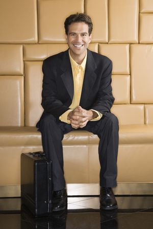 Caucasian businessman with briefcase smiling at viewer. Stock Photo - 2622886