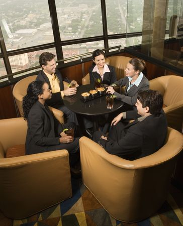 Ethnically diverse businesspeople sitting at table in restaurant talking. photo