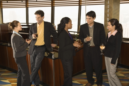 horizontal bar: Ethnically diverse group of businesspeople in bar drinking and conversing.