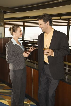 Caucasian business man and woman standing in bar with alcoholic beverages. photo