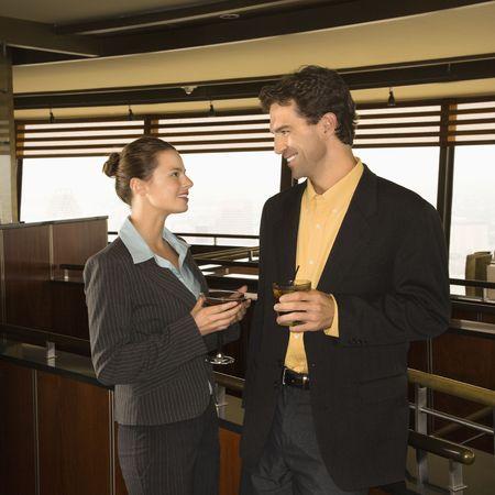bebidas alcoh�licas: Cauc�sica el hombre y la mujer de negocios conversiting con bebidas alcoh�licas.
