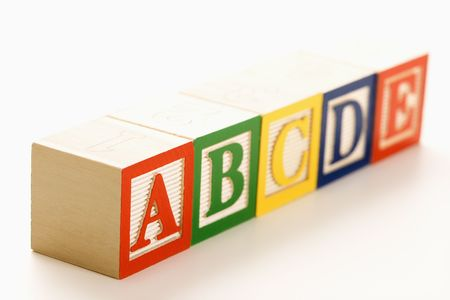 lined up: Alphabet blocks lined up in a row. Stock Photo