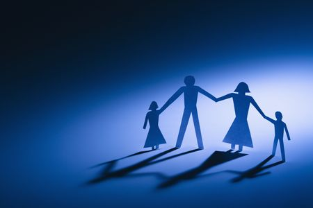 Paper cutout  of four standing holding hands.
