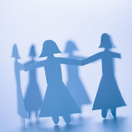 girls holding hands: Paper cutout girls holding hands standing in circle. Stock Photo