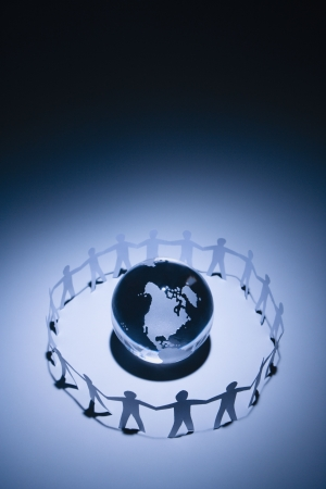 Cutout paper people standing around globe holding hands. Stock Photo - 2616853